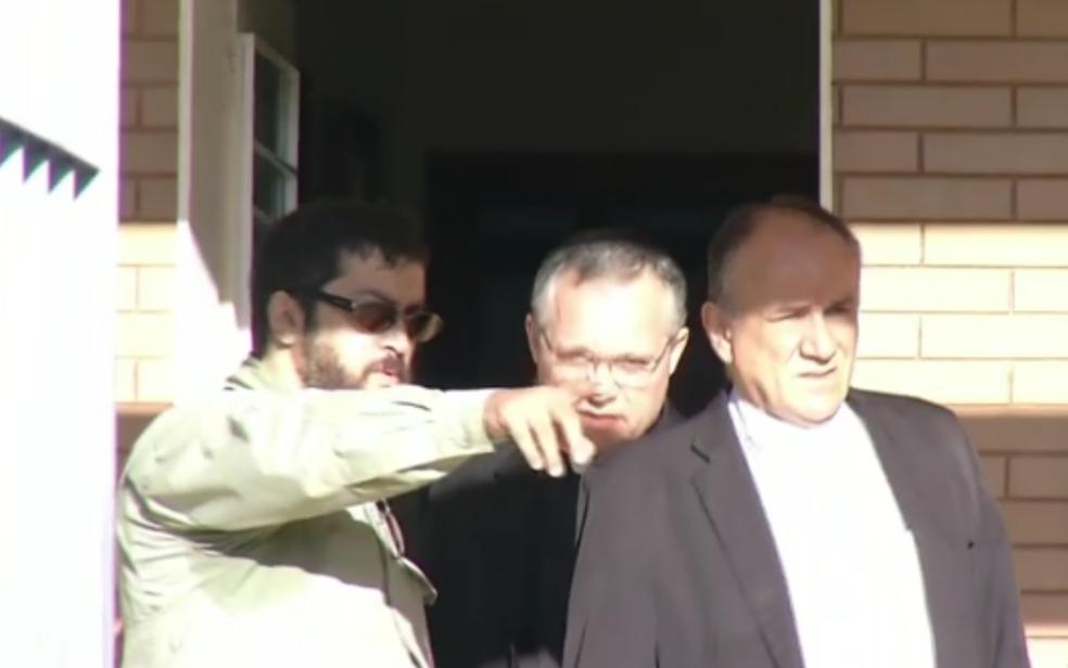 O promotor do Ministério Público de Goiás Douglas Chegury (verde) aponta direção para o bispo Dom José Ronaldo (à frente) e o juiz eclesiástico Tiago Wenceslau (atrás), presos em operação que investiga desvio de dízimo (Foto: Reprodução/TV Anhanguera)