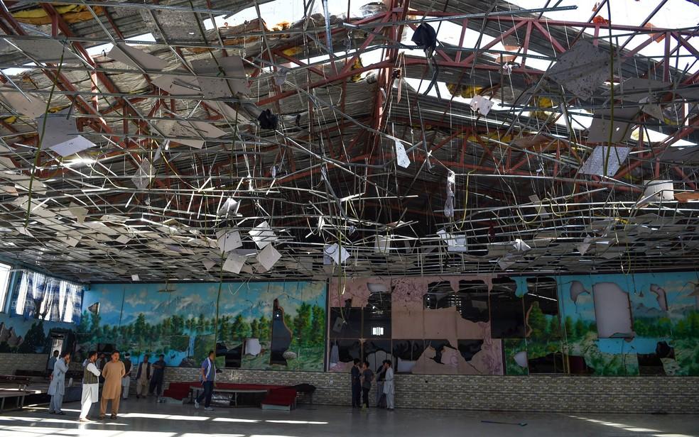 Afegãos investigam interior de salão de festas após explosão  — Foto: Wakil Kohsar / AFP Photo