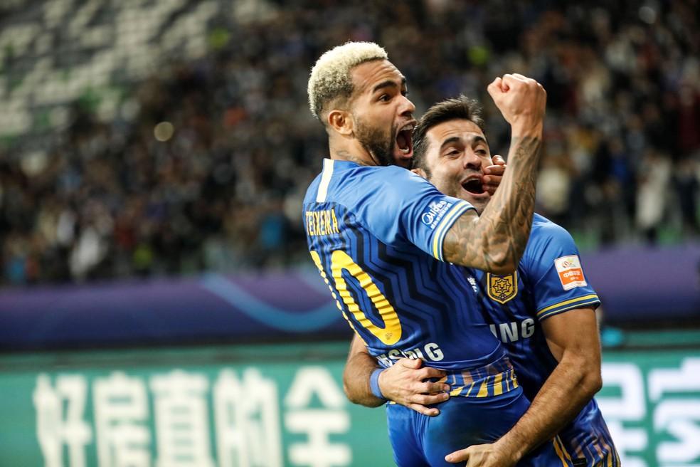 Alex Teixeira e Eder comemoram gol do Jiangsu Sunning — Foto: AFP