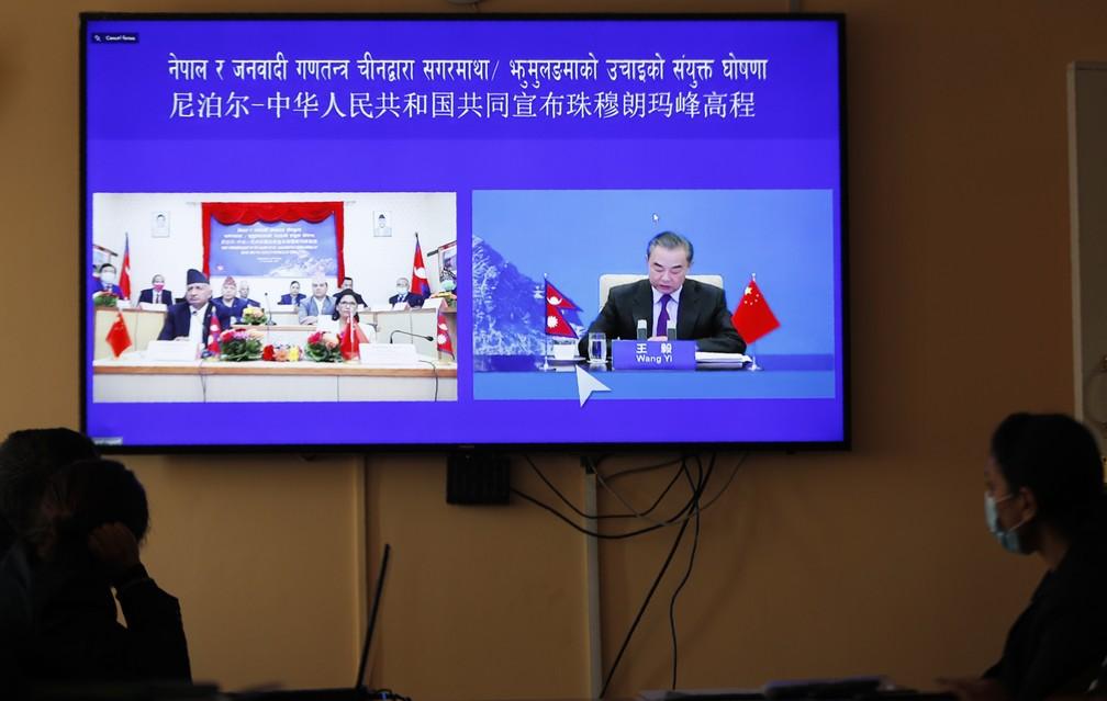 Ministros das Relações Exteriores da China e do Nepal divulgam a nova altura do Monte Everest em uma transmissão virtual — Foto: Niranjan Shrestha/AP