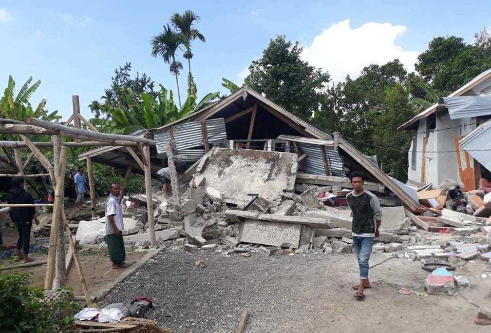 Residentes caminham junto a casas destruídas em zona afetada por terremoto, na aldeia de Sajang, na Indonésia (Foto: Rosidin/AP Foto)