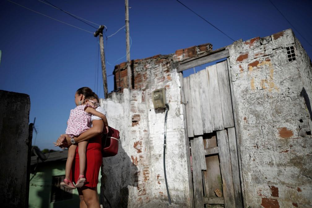 Gleyse Kelly da Silva, de 28, segura a filha de dois anos Maria Giovanna, na casa onde moram no Recife — Foto: Ueslei Marcelino/Reuters