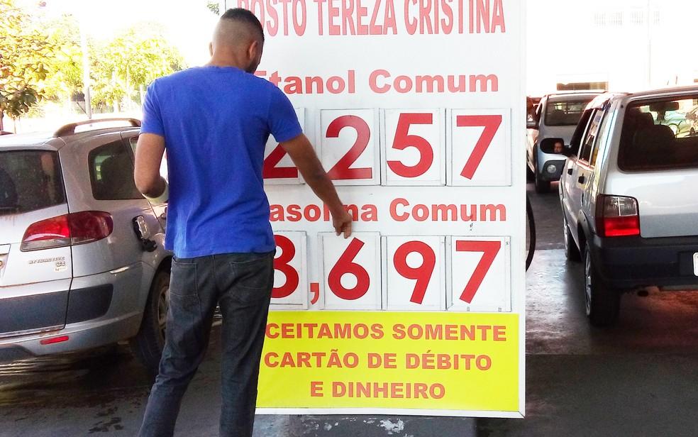 Funcionário muda preço de gasolina em placa de posto de combustível em Belo Horizonte (Foto: Alex Araújo/G1)