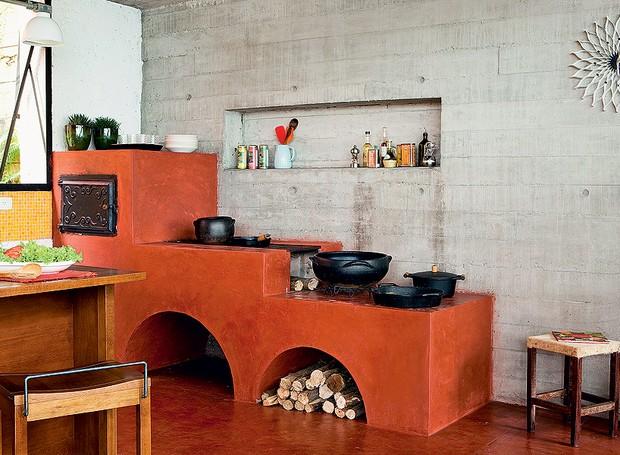 A tradicional dupla de fogão e forno à lenha tem acabamento de cimento queimado com pó Xadrez vermelho, herança da arquitetura rural. Em contraste, nada mais urbano que a parede de concreto armado aparente. Projeto do escritório Brasil Arquitetura (Foto: Edu Castello/Casa e Jardim)