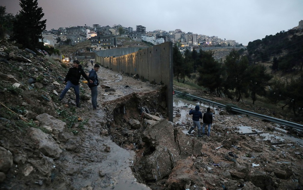 Palestinos são vistos perto de parte de uma barreira que desabou após fortes chuvas, próximo ao campo de refugiados de Shuafat, em Jerusalém Oriental, na quinta-feira (26) (Foto: Reuters/Ammar Awad)
