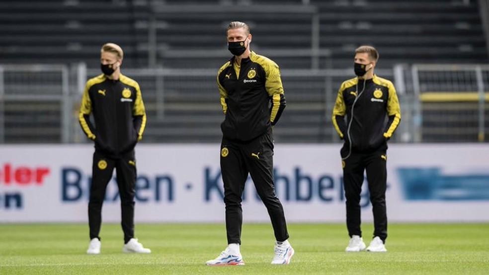 todos de máscara, jogadores do Borussia Dortmund pisam no campo antes da partida  — Foto: Reprodução/Twitter
