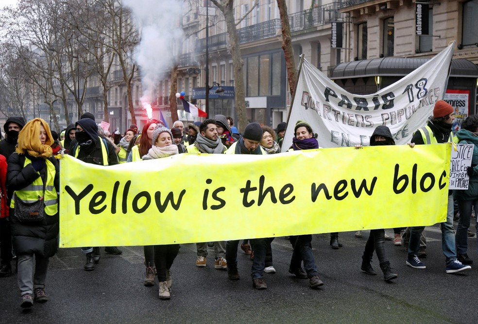 """Manifestantes em rua de Paris carregam faixas ligando os coletes amarelos ao filme francês """"Azul é a cor mais quente"""" — Foto: Charles Platiau/Reuters"""