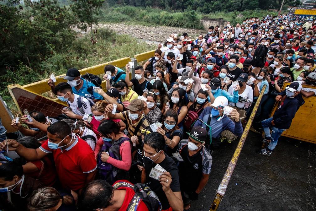 12 de março - Pessoas vindas da Venezuela utilizam máscaras protetoras como medida de precaução para evitar contrair o novo coronavírus COVID-19 na fronteira na Ponte Internacional Simon Bolivar em Cucuta, na Colômbia. O país declarou uma 'Emergência em Saúde' devido à nova pandemia de coronavírus, que lhe permite tomar medidas excepcionais como proibir o desembarque de navios de cruzeiro e a realização de eventos públicos com mais de 500 pessoas — Foto: Schneyder Mendoza/AFP