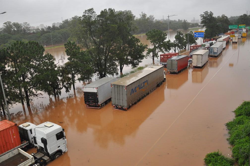 Caminhões ficaram parados em meio à água na Marginal Pinheiros, após o rio transbordar devido à chuva em São Paulo — Foto: Antônio Cícero/Photopress/Estadão Conteúdo