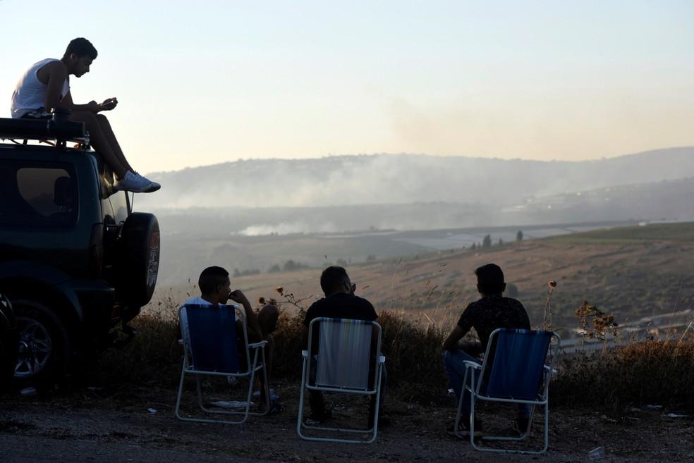 Israelenses assistem ao fogo provocado por tiros na fronteira Líbano-Israel neste domingo (1).  — Foto: Rami Shlush/Reuters