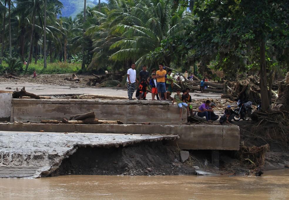 Moradores sobre ponte destruída após inundações repentinas em Salvador, Lanao del Norte, nas Filipinas (Foto: REUTERS/Richel V. Umel)