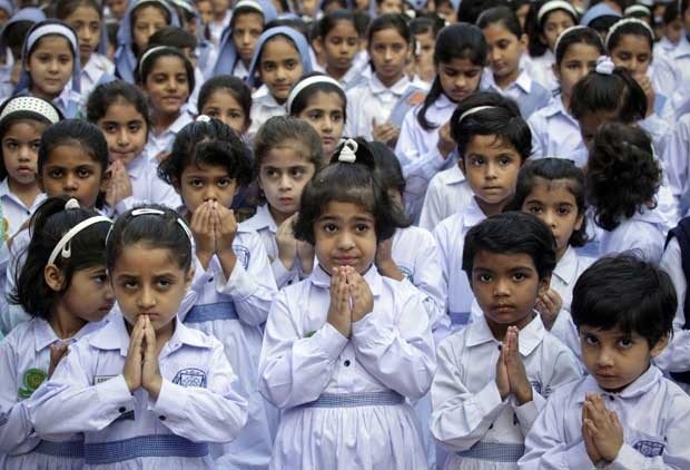 Meninas de escola em Lahore, Paquistão, rezam nesta sexta-feira (19) pela recuperação de Malala (Foto: AP)