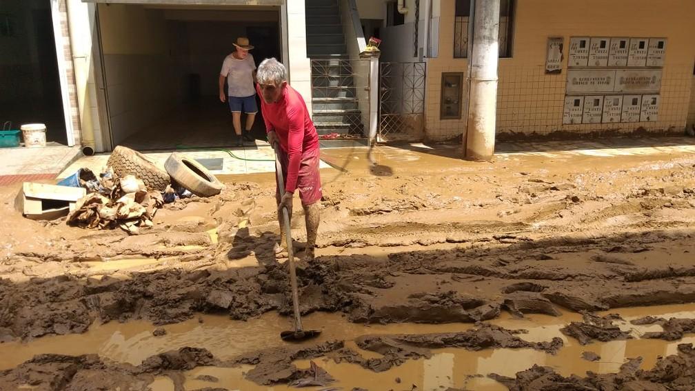 Morador de Alfredo Chaves puxa lama de rua, no Sul do ES  — Foto: Kaique Dias/ TV Gazeta