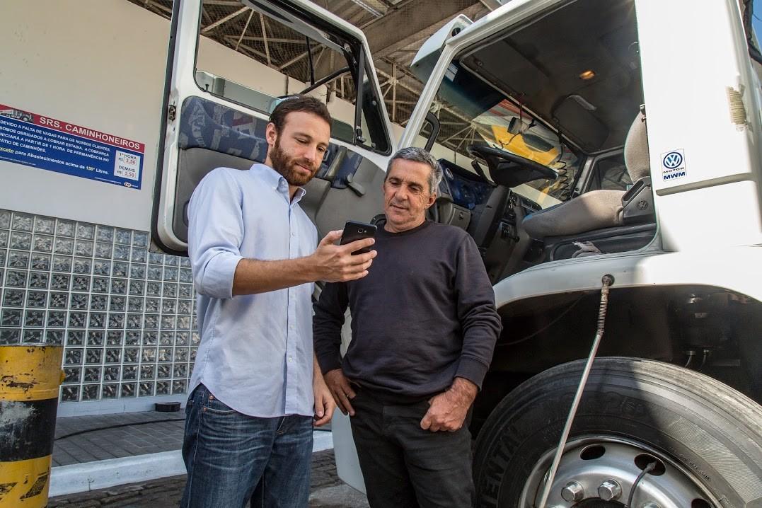 O diretor de operações da FreteBras, Bruno Hacad, ao lado de um caminhoneiro, com um celular à mão. A startup conta com mais de 500 mil caminhoneiros em sua comunidade (Foto: Divulgação/FreteBras)