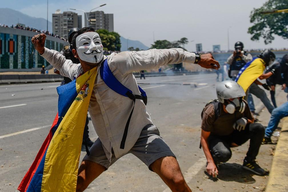 Manifestantes antigovernamentais colidem com forças de segurança nos arredores da base militar de La Carlota, em Caracas, em 1º de maio  — Foto: Matias Delacroix / AFP