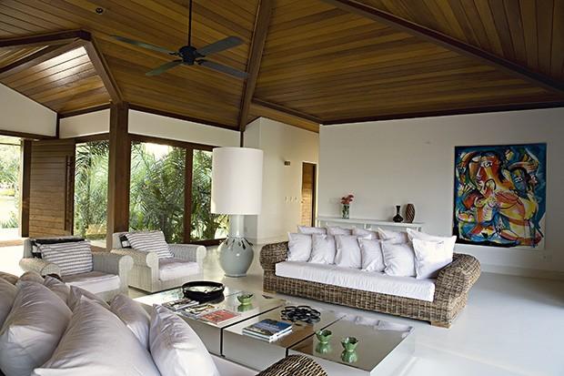 A sala de estar desta casa de praia tem grandes aberturas de canto com vidro para o jardim. Projeto do arquiteto David Bastos (Foto: Tuca Reinés / Casa e Jardim)