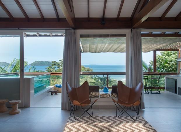 Da sala de estar, avista-se a piscina de vidro na varanda e, mais adiante, o mar  (Foto: Cacá Bratke/Divulgação | Produção Deborah Apsan)