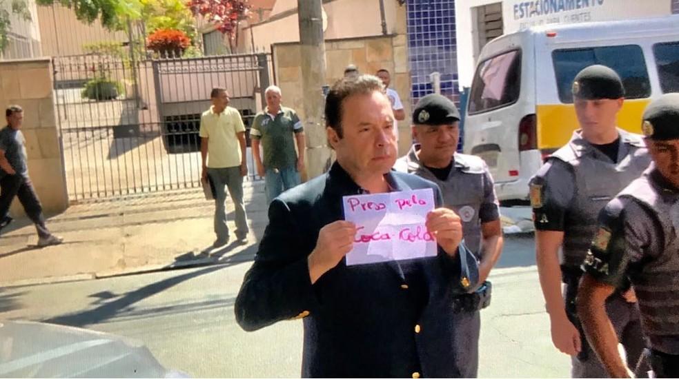 """Laerte Codonho, dono da empresa de refrigerantes Dolly, chega à delegacia com papel no qual se lê """"preso pela Coca-Cola"""" (Foto: Amós Alexandre/GloboNews)"""