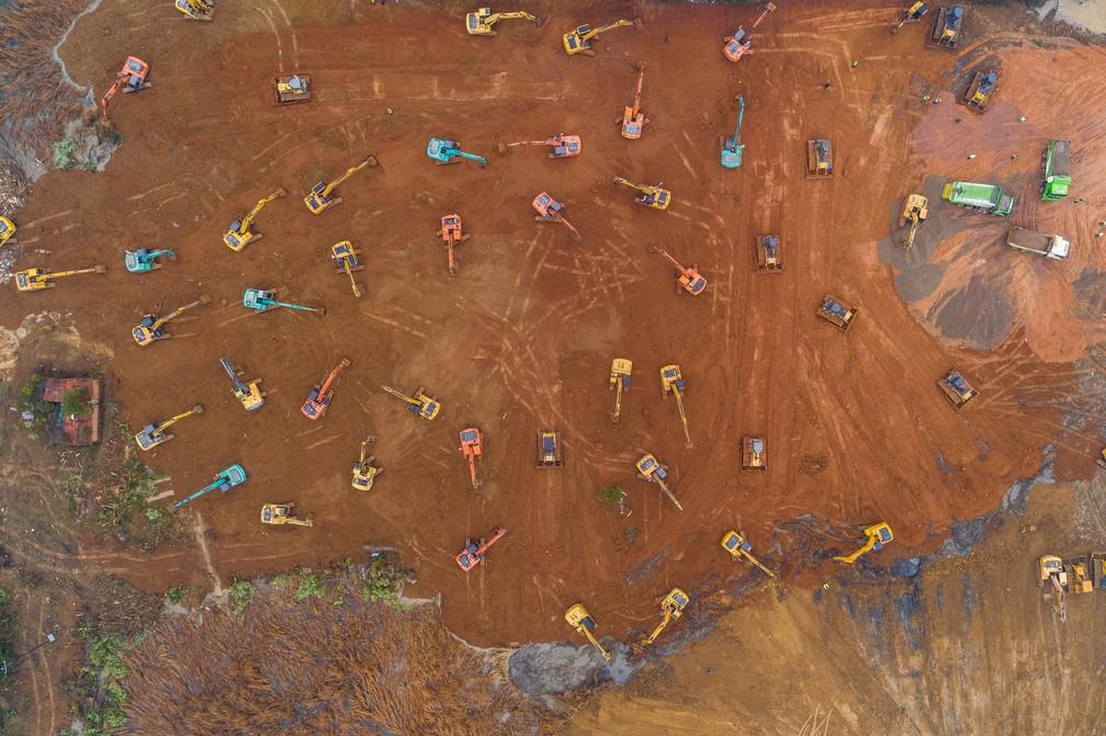 Foto aérea mostra escavadeiras no canteiro de obras do novo hospital dedicado a pacientes do novo coronavírus em Wuhan. — Foto: STR/AFP