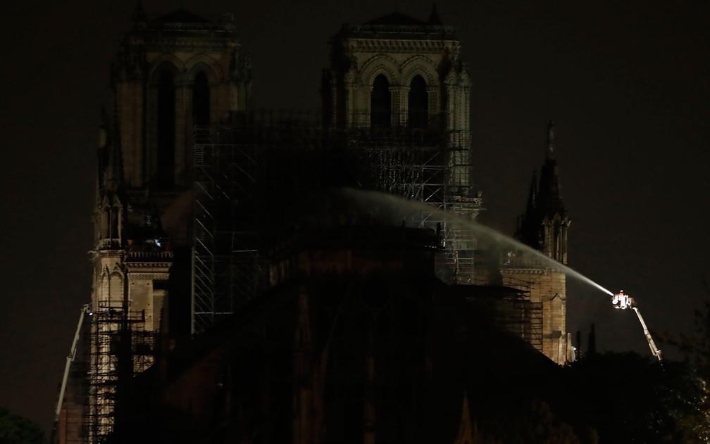 Bombeiros jogam água na fachada da Catedral de Notre-Dame, em Paris, na madrugada de terça-feira (16), após controlarem incêndio no local — Foto: Zakaria Abdelkafi/AFP