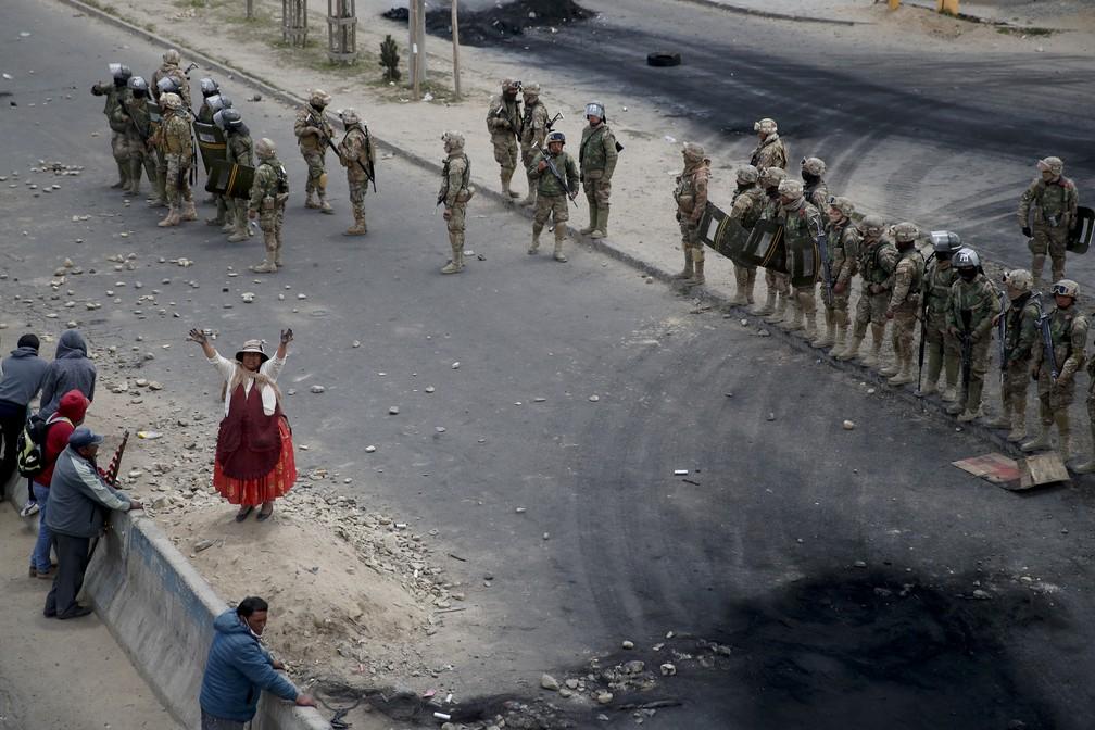 Manifestante acena em frente a militares em operação para liberar acesso de rodovias de El Alto, na Bolívia, nesta terça-feira (19) — Foto: Natacha Pisarenko/AP Photo