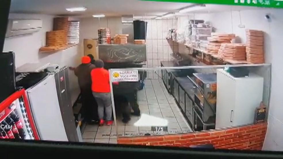 Câmeras mostram grupo cercando policial atrás de porta em pizzaria de Porto Alegre — Foto: Reprodução/RBS TV