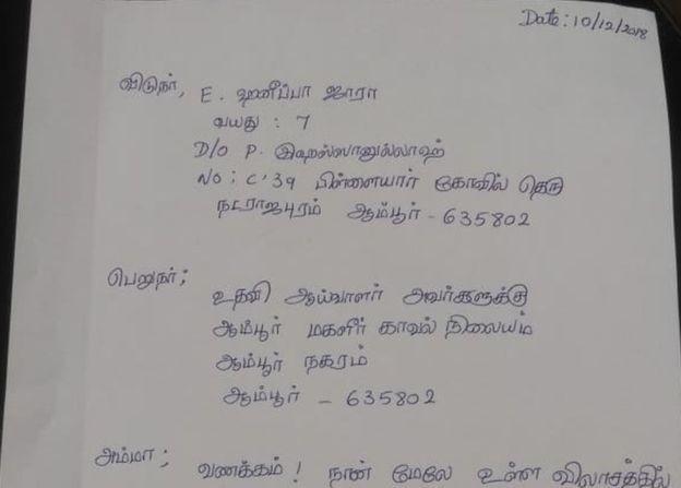 A menina juntamente com o pai prestando esclarecimentos à polícia. Detalhe para os troféus na mesa da autoridade (Foto: Reprodução BBC Tamil)