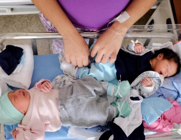 Aqui, os gêmeos Matheo e Mayha dividem o mesmo leite (Foto: Reuters/Marco Bello)