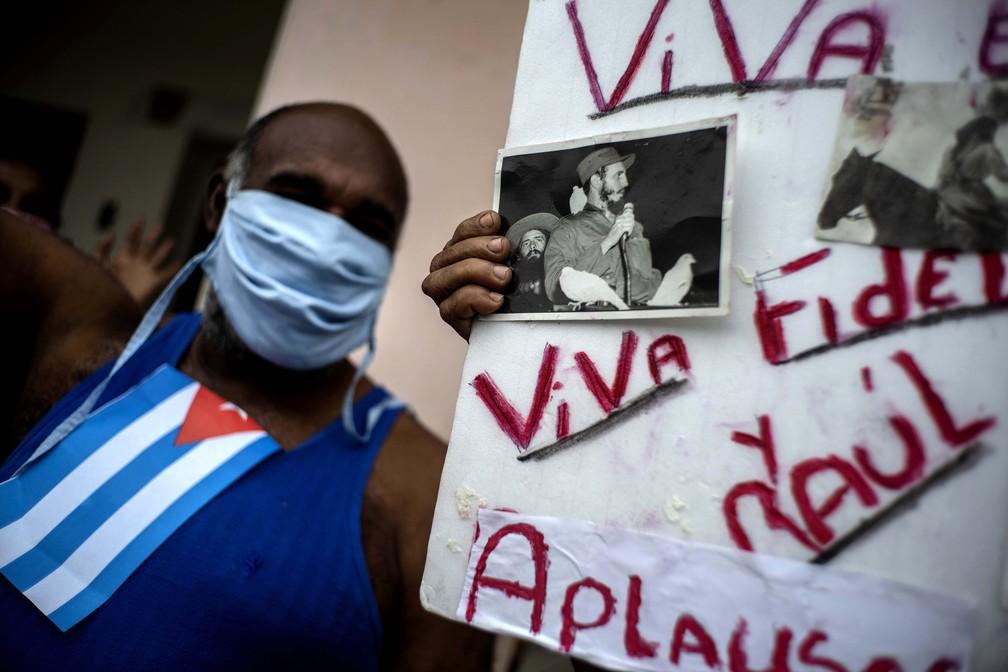 Homem com máscara de proteção comemora o Dia Internacional do Trabalho enquanto outra pessoa segura uma placa com fotos de heróis revolucionários e a mensagem 'Viva Fidel e Raul', em Havana, Cuba — Foto: Ramon Espinosa/AP