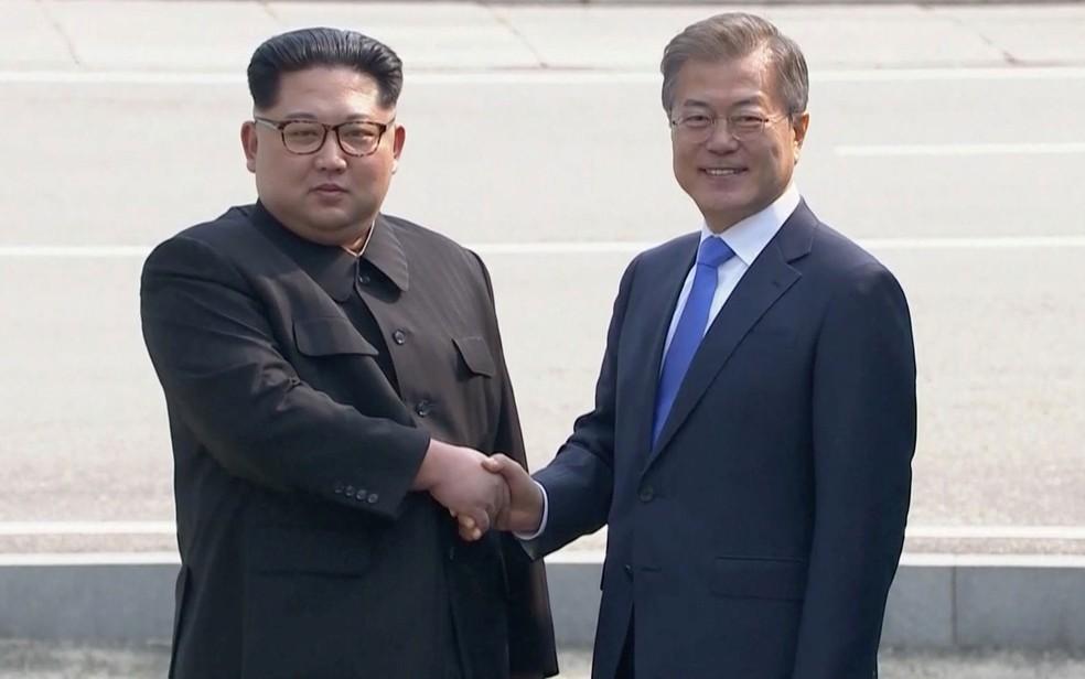 O líder norte-coreano Kim Jong-un cumprimenta o presidente sul-coreano Moon Jae-in ao chegar na Zona Desmilitarizada, em abril. (Foto: Host Broadcaster via Reuters)