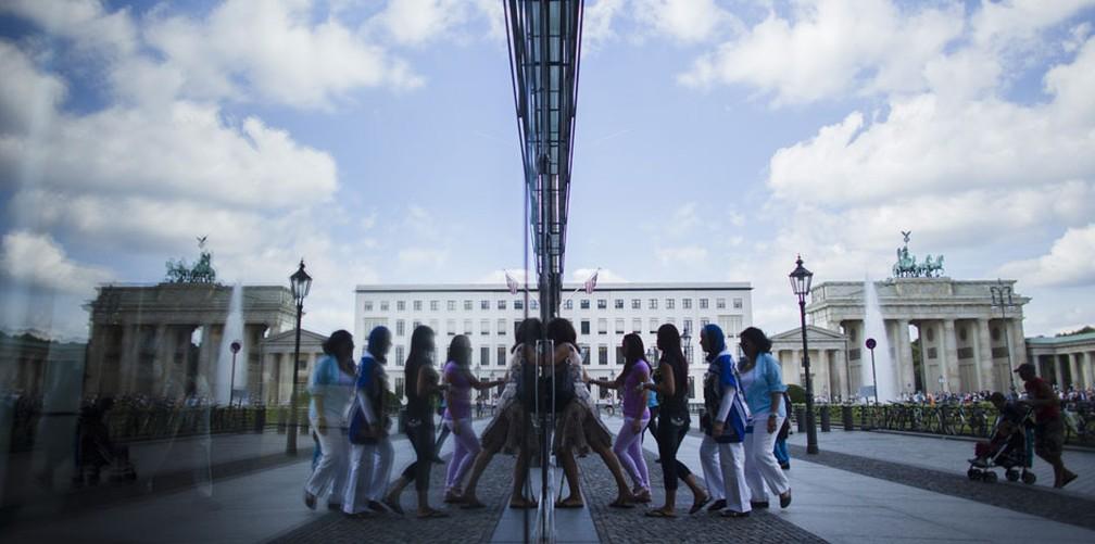 Pessoas são refletidas em janela em frente ao Portão de Brandemburgo, ponto turístico de Berlim, na Alemanha. — Foto: Markus Schreiber/AP