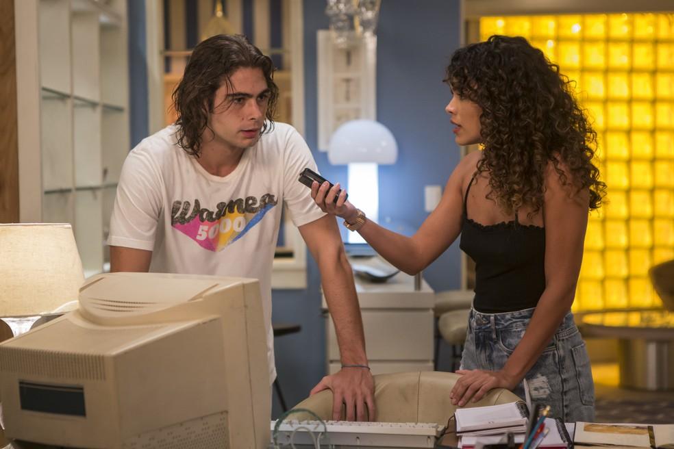 Moana (Giovanna Cordeiro) mostra a mensagem de Nicole para João (Rafael Vitti) em Verão 90 — Foto: Artur Meninea/Gshow