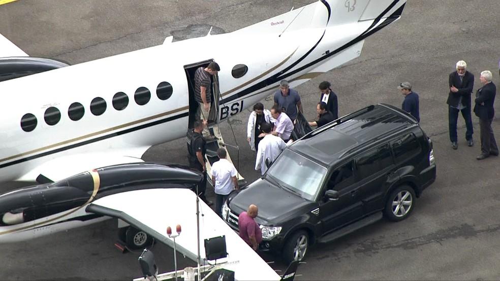 Paulo Maluf, de camisa rosa, deixa carro para entrar em avião (Foto: TV Globo/Reprodução)