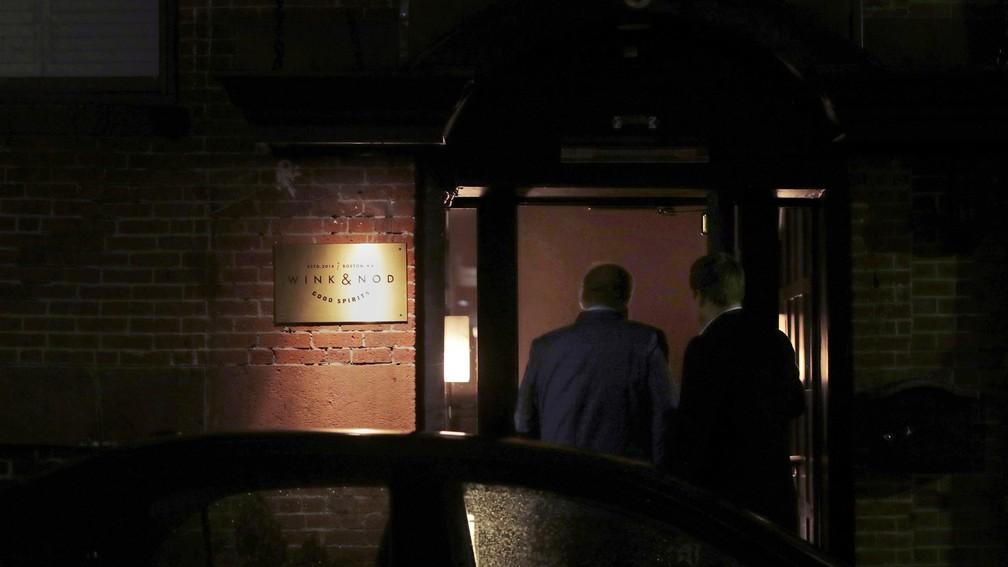 Dois clientes são vistos através entrada pouco iluminada do Wink & Nod, um bar no estilo dos ilegais da época da Proibição, em Boston, em 10 de dezembro de 2019 — Foto: AP Photo/Charles Krupa