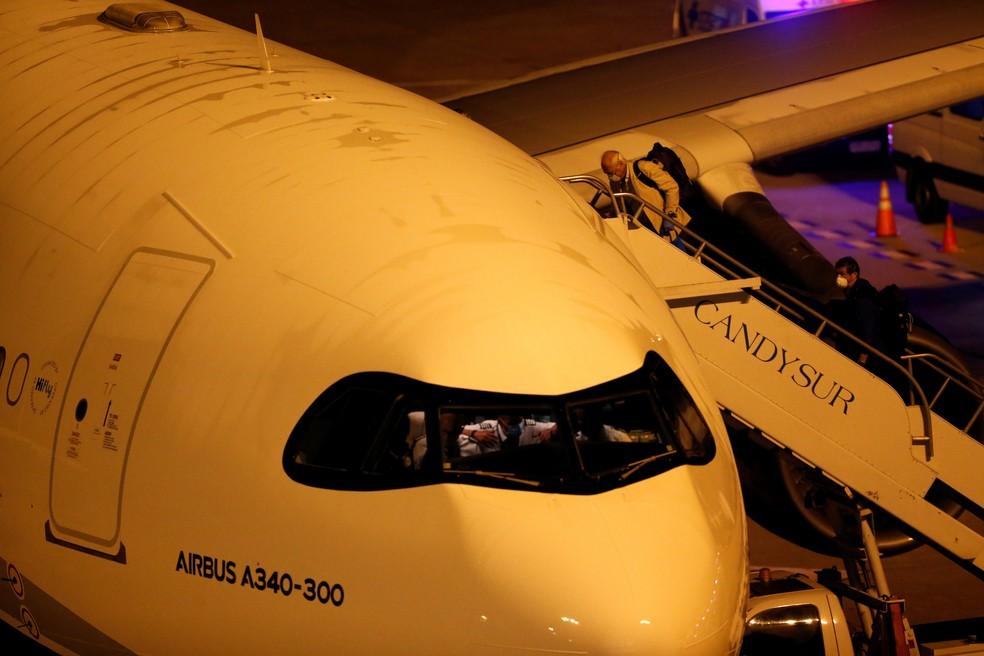 Passageiros australianos e neozelandeses que deixaram o navio de cruzeiros Greg Mortimer embarcam em uma aeronave no aeroporto de Montevidéu, no Uruguai, neste sábado (11)  — Foto: Mariana Greif/ Reuters