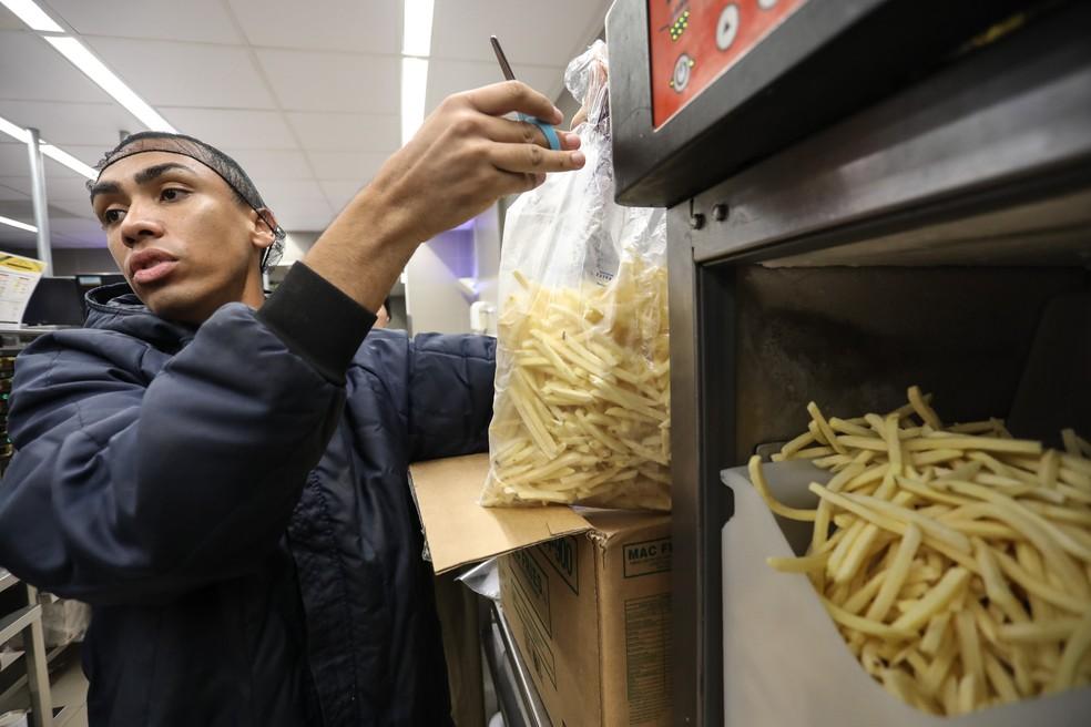 Funcionário do McDonald's despeja batata em dispensador (Foto: Fábio Tito/G1)