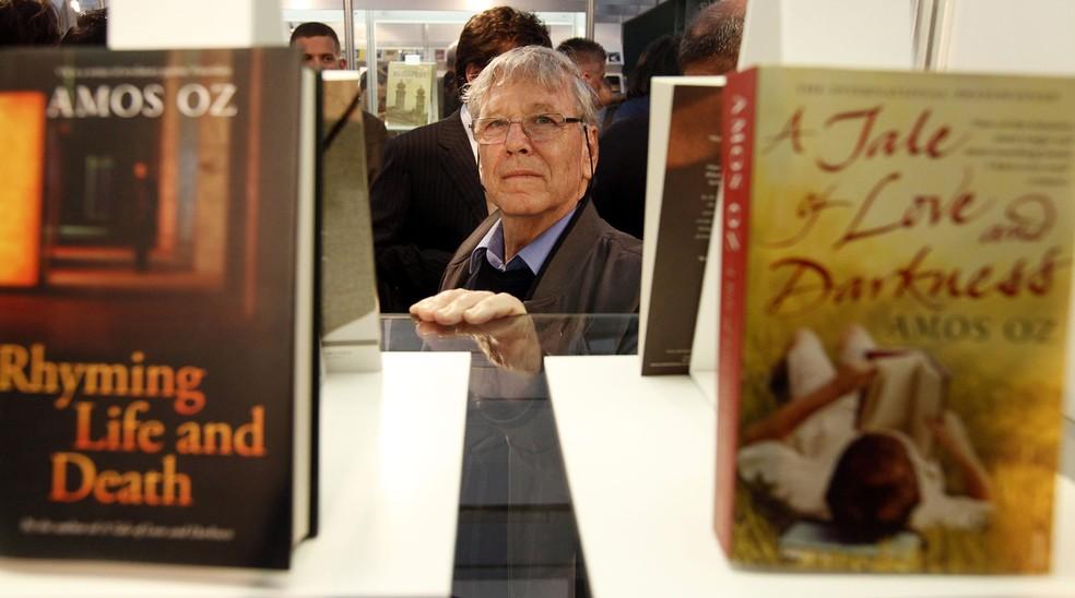 O escritor israelense Amos Oz, o principal convidado da feira anual de livros de Budapeste, posa entre seus livros no salão do Centro Cultural Millenaris. Foto de abril de 2010 — Foto: Gergely Botar/AFP/Arquivo