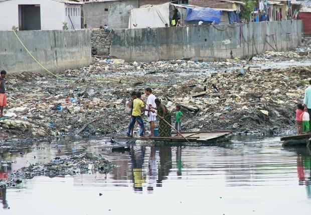 Balsa que atravessa o canal de esgoto em uma favela da Índia (Foto: BBC News)