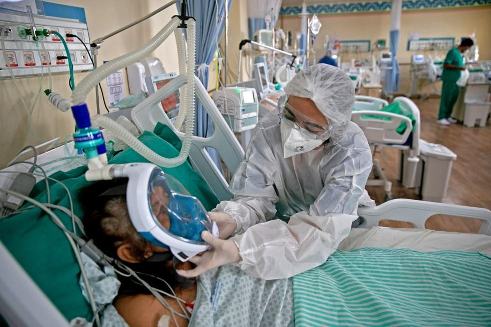 Profissional de saúde ajusta máscara de oxigênio de paciente com Covid-19 em hospital de Belém com leitos exclusivos para a Covid, no dia 26 de março. — Foto: Tarso Sarraf/AFP