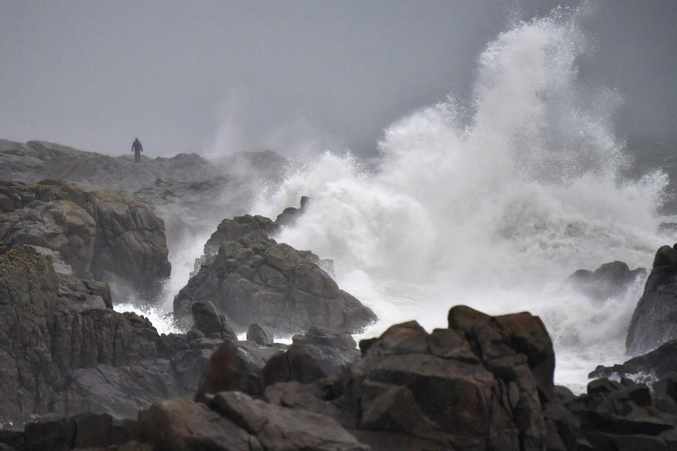 Homem observa fortes ondas em  Batz-sur-Mer, na França, neste domingo (31), véspera da chegada da tempestade Carmen no país — Foto: LOIC VENANCE / AFP