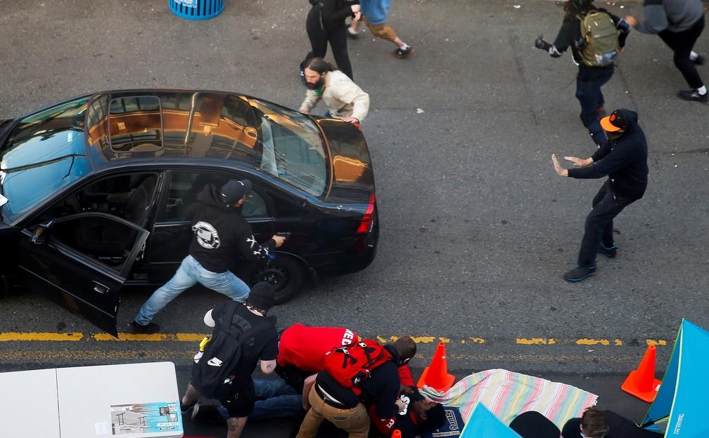 Um homem carregando uma arma sai de um veículo enquanto Daniel Gregory é atendido por médicos após ser baleado no braço por um motorista que tentou dirigir no meio de um protesto contra a desigualdade racial após a morte de George Floyd sob a custódia da polícia de Minneapolis, em Seattle, Washington, EUA, em 7 de junho  — Foto: Lindsey Wasson/Reuters