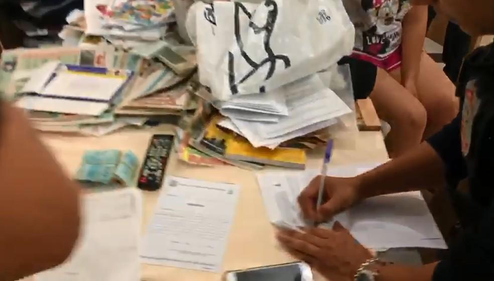Policiais cumprindo buscas em uma das casas alvo da operação contra venda ilegal de lotes no DF — Foto: Reprodução