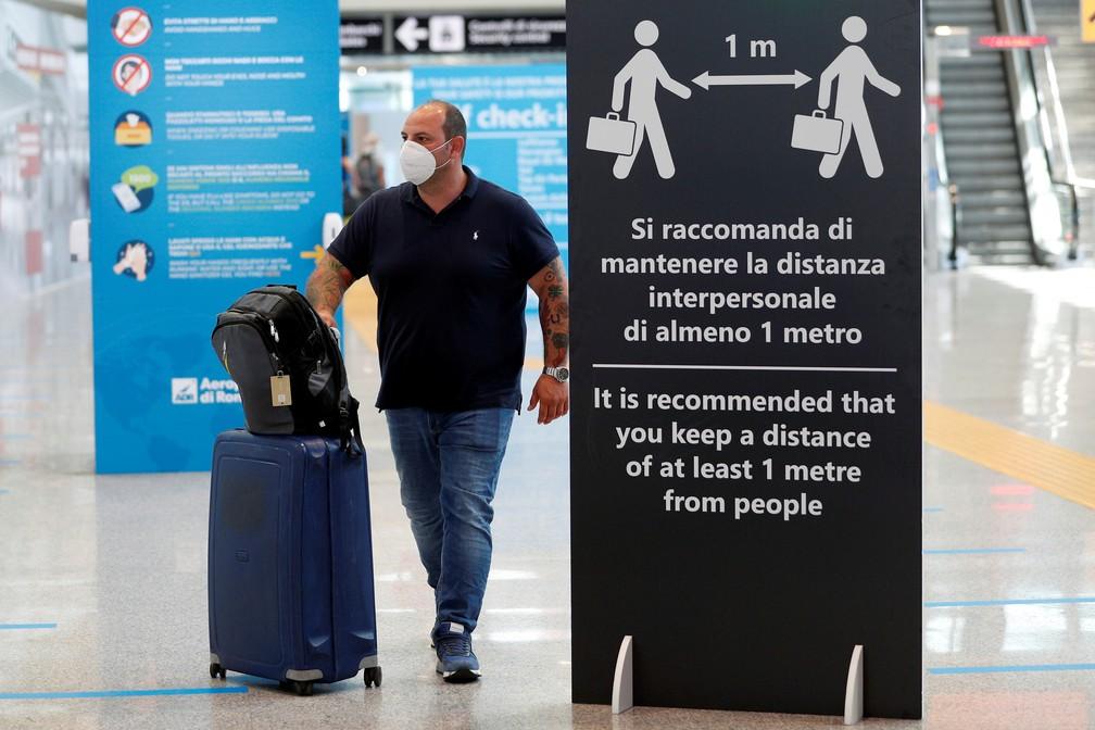 30 de junho - Passageiro com máscara caminha ao lado de placa que pede distanciamento social no aeroporto de Fiumicino, perto de Roma, na Itália — Foto: Guglielmo Mangiapane/Reuters