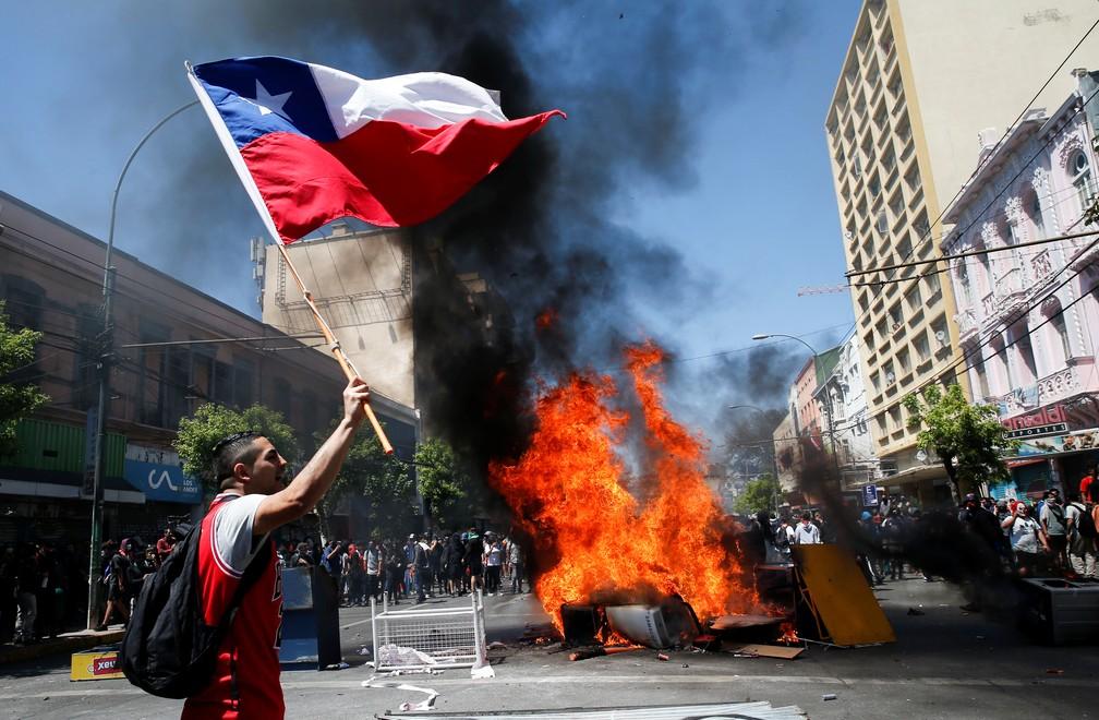 Manifestante empunha bandeira do Chile em barricada em Valparaiso, nesta quinta-feira (24) — Foto: Rodrigo Garrido/Reuters