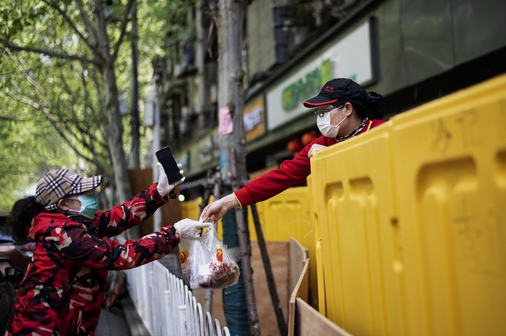 6 de abril - Um fornecedor entrega comida para uma cliente por cima de uma barricada, em Wuhan, província central de Hubei, na China — Foto: Noel Celis/AFP