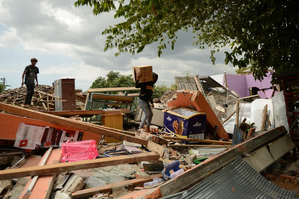 -  Pessoas procuram pertences no meio dos destroços de uma casa que desabou em Kayangan, no norte da ilha de Lombok, na Indonésia, após forte terremoto