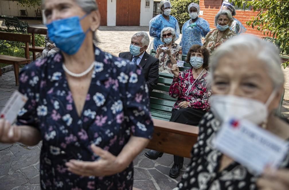 Chilenas mostram seus cartões de vacinação atualizados após receberem a 2ª dose da CoronaVac, vacina contra a Covid-19 do laboratório Sinovac, em um asilo em Santiago, no Chile, em 5 de março de 2021. Entre elas, sentado, está o Ministro da Saúde do Chile, Enrique Paris  — Foto: Esteban Felix/AP