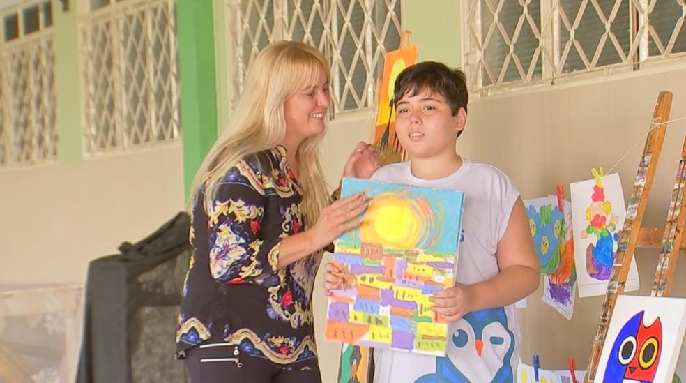 Danilo com a mãe, Eliane, e o quadro que ganhou o prêmio — Foto: Reprodução/TV TEM
