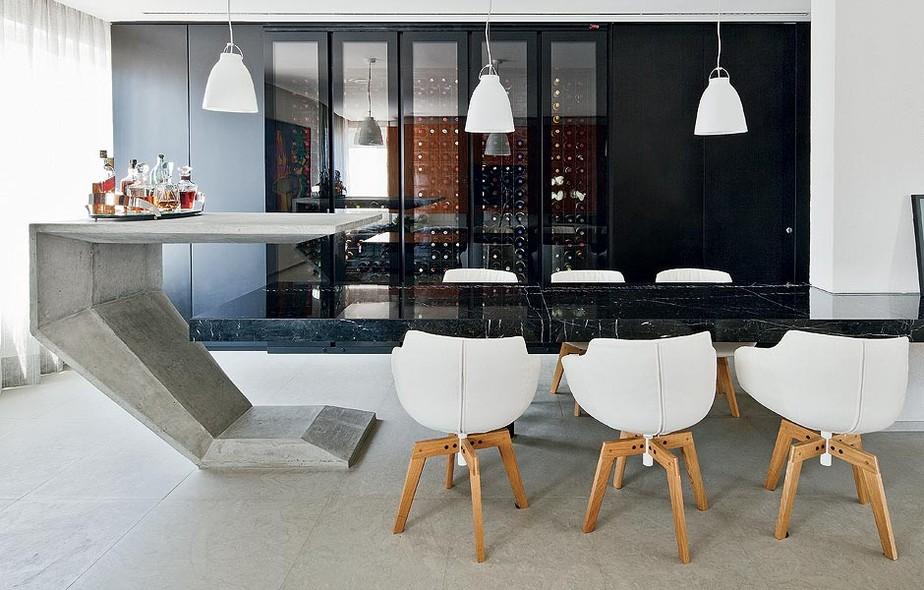 Com a redução da cozinha, que recortava parte do living, os arquitetos Paula Zemel e Eduardo Chalabi conseguiram espaço para instalar uma adega climatizada voltada para a sala de jantar. Ela fica em painel preto, que camufla a porta do lavabo