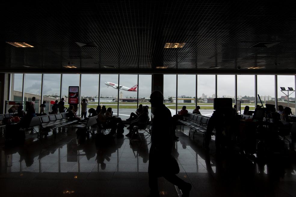 Pessoas na sala de embarque do aeroporto de Congonhas, em São Paulo, enquanto um aviao da TAM (LATAM) decola ao fundo — Foto: Marcelo Brandt/G1
